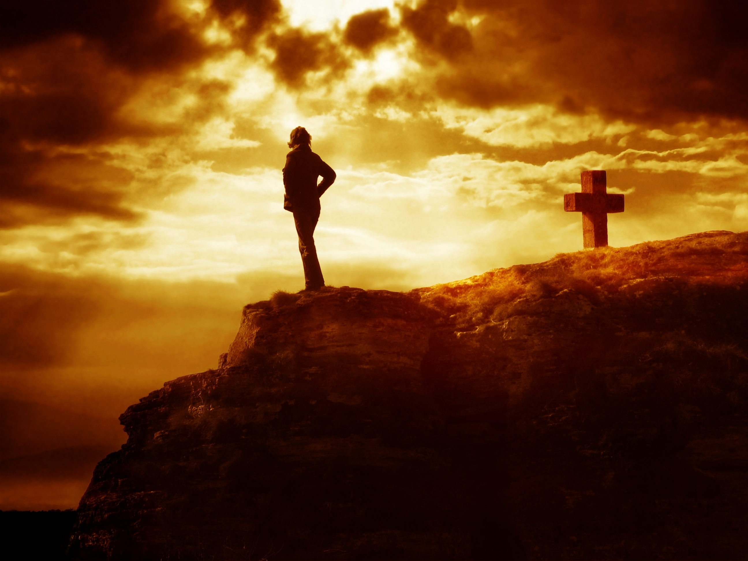 Dramatic sky scenery with a mountain cross and a thinking person. A symbol of heavy inner struggles. Where to go? What do you say?
