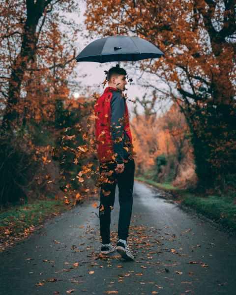 photo of man holding an umbrella